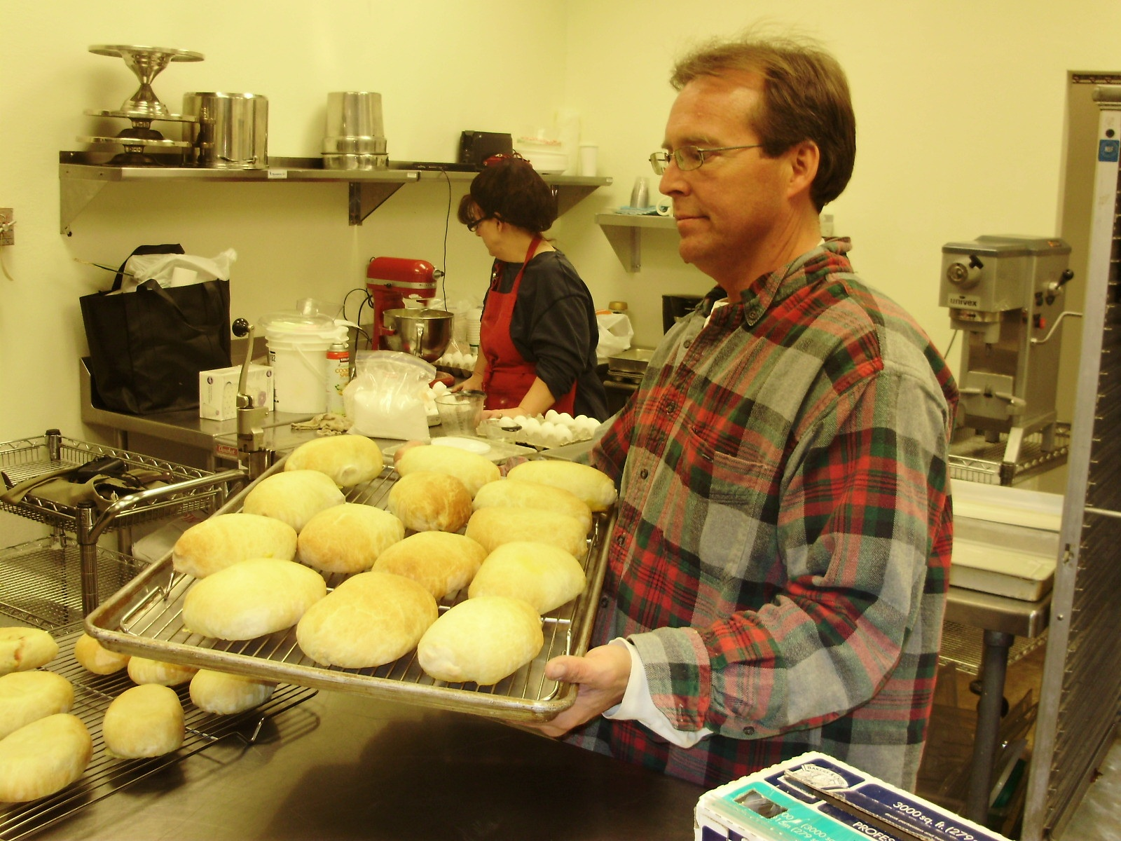 Photo by Steven SaintBesides providing kitchen space for local food producers, Jerry Downing (front) makes his own pocket sandwich lie at Gotta Love It! Kitchen. Care Young (back) is getting ready to cater a wedding.